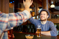 Amis masculins heureux faisant la haute cinq à la barre ou au bar Images libres de droits