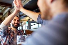 Amis masculins heureux faisant la haute cinq à la barre ou au bar Photographie stock