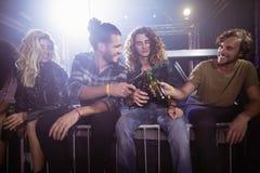 Amis masculins heureux grillant des bouteilles à bière Image libre de droits