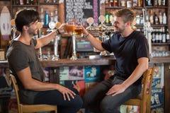 Amis masculins heureux grillant des tasses de bière dans la barre Photographie stock libre de droits