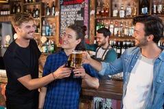 Amis masculins heureux grillant les tasses et la bouteille de bière Photographie stock libre de droits