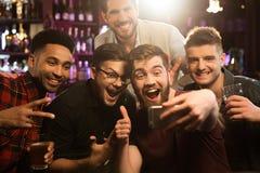 Amis masculins heureux prenant le selfie et buvant de la bière Photos libres de droits