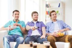 Amis masculins heureux regardant la TV à la maison Images stock