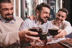 Amis masculins heureux soulevant leurs verres Images stock
