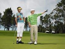 Amis masculins jouant au golf ensemble Images libres de droits