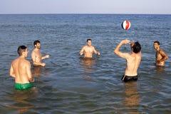 Amis masculins jouant la boule en mer Photos stock