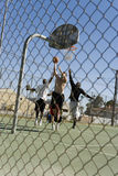 Amis masculins jouant le basket-ball sur la cour Photographie stock