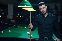 Amis masculins jouant le jeu de billard dans le club Photographie stock libre de droits