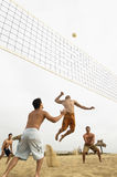 Amis masculins jouant le volleyball sur la plage Photos stock