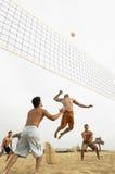 Amis masculins jouant le volleyball sur la plage Photos stock