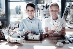 Amis masculins joyeux construisant les machines robotiques Photographie stock