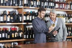 Amis masculins lisant le label des bouteilles de vin dans la boutique Photos libres de droits