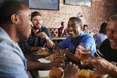 Amis masculins mangeant dans la barre de sports avec des écrans dedans derrière Photo stock