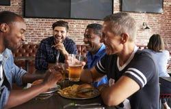 Amis masculins mangeant dans la barre de sports avec des écrans dedans derrière Photos libres de droits