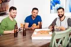 Amis masculins mangeant de la pizza à la maison Images stock