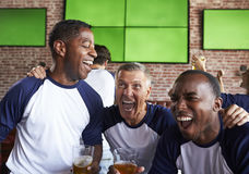 Amis masculins observant le jeu dans la célébration de barre de sports Image libre de droits
