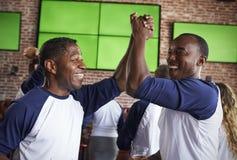 Amis masculins observant le jeu dans la célébration de barre de sports Photo stock
