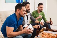 Amis masculins observant un jeu de football Photos libres de droits