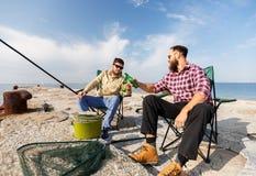 Amis masculins pêchant et buvant de la bière sur la jetée de mer image stock
