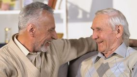 Amis masculins pluss âgé parlant et étreignant, rencontrant des frères, salutation de vacances banque de vidéos
