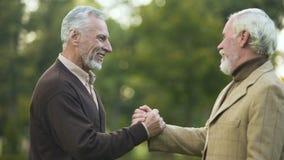 Amis masculins pluss âgé se serrant la main et étreindre, rencontrant des frères, salutation banque de vidéos