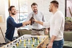 Amis masculins positifs buvant de la bière Photos libres de droits