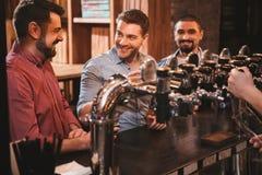 Amis masculins positifs parlant au compteur de barre Photographie stock libre de droits