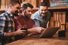 Amis masculins positifs s'asseyant devant l'ordinateur portable Images stock