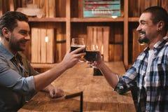 Amis masculins positifs s'asseyant vis-à-vis de l'un l'autre Image libre de droits