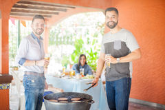 Amis masculins profitant d'un agréable moment grillant des hamburgers Photographie stock libre de droits