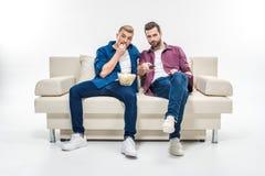 Amis masculins regardant la TV Image stock