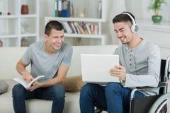 Amis masculins riant nerveusement sur ce qu'elles ont vu sur l'Internet Photos stock