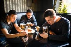 Amis masculins s'asseyant dans des smartphones buvant de la bière à la barre ou au bar La dépendance de Smartphones Photos stock