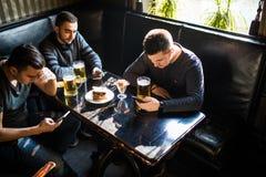 Amis masculins s'asseyant dans des smartphones buvant de la bière à la barre ou au bar La dépendance de Smartphones Photo stock