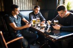 Amis masculins s'asseyant dans des smartphones buvant de la bière à la barre ou au bar La dépendance sociale de réseau de Smartph Photographie stock