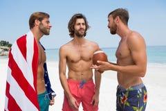Amis masculins sans chemise parlant tout en se tenant à la plage Photo stock