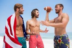 Amis masculins sans chemise parlant tout en se tenant contre le ciel clair Photos stock