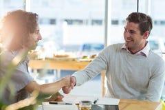 Amis masculins se serrant la main dans le café Images stock