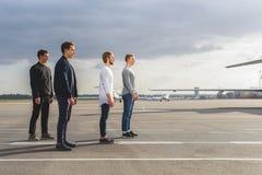 Amis masculins se tenant à l'aéroport dehors Photos libres de droits
