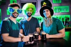 Amis masculins souriant et tenant des tasses de bière Photographie stock
