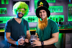 Amis masculins souriant et tenant des tasses de bière Images stock