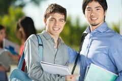 Amis masculins souriant sur le campus d'université Images libres de droits