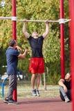 Amis masculins sportifs établissant sur un fond brouillé de parc Concept de vêtements de sport Images stock