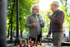 Amis masculins supérieurs joyeux appréciant la boisson chaude extérieure Image stock