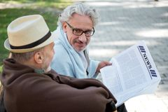 Amis masculins supérieurs joyeux lisant le journal Photo libre de droits