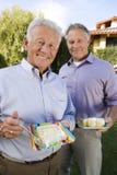 Amis masculins supérieurs mangeant le gâteau Photo libre de droits