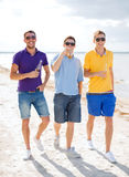 Amis masculins sur la plage avec des bouteilles de boisson Photos libres de droits