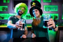 Amis masculins tenant des tasses de bière Photographie stock libre de droits