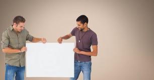 Amis masculins tenant le panneau d'affichage vide sur le fond beige Images libres de droits