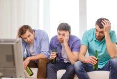 Amis masculins tristes avec des sports de observation de bière Images libres de droits